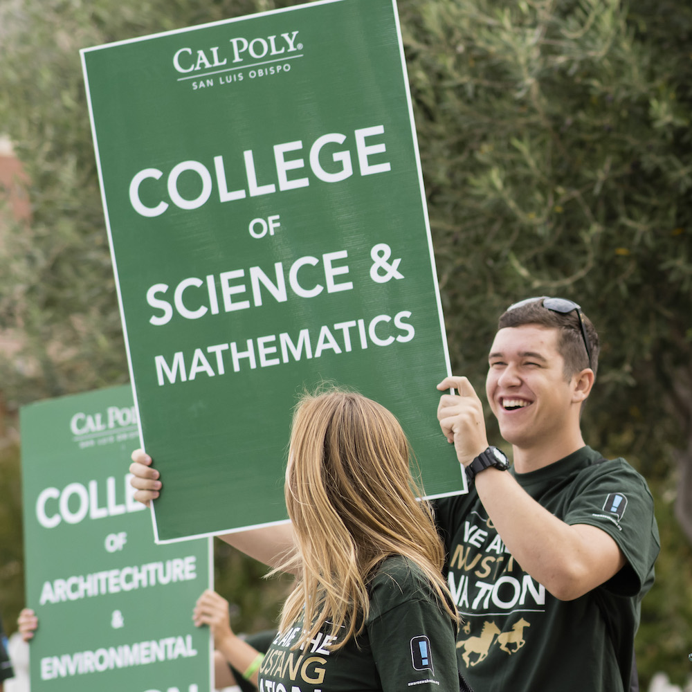 "Students hold a green ""College of Science & Mathematics"" sign"