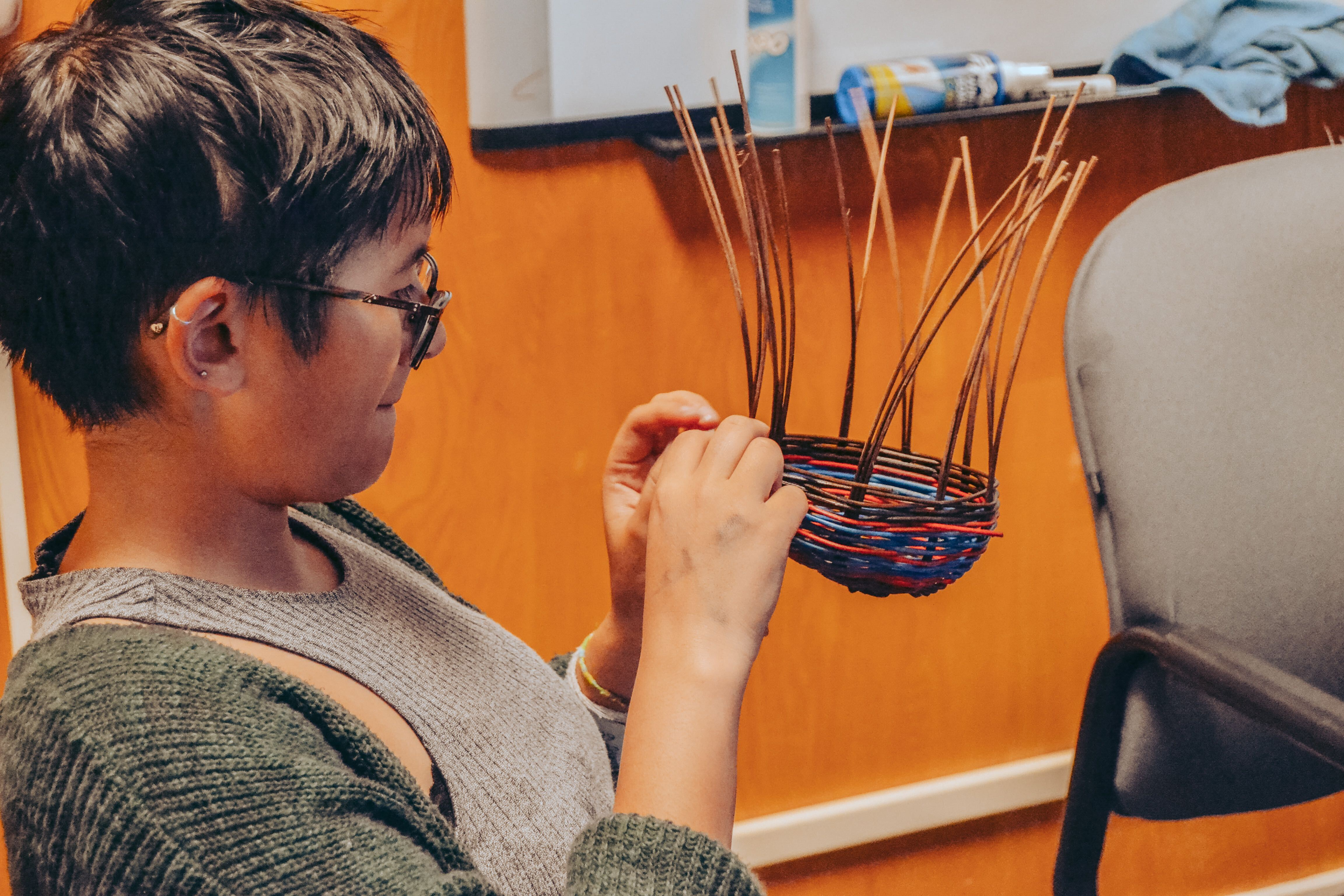 Picture of student weaving basket.