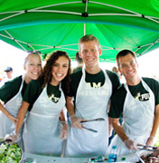 Cal Poly students under green umbrella serving food