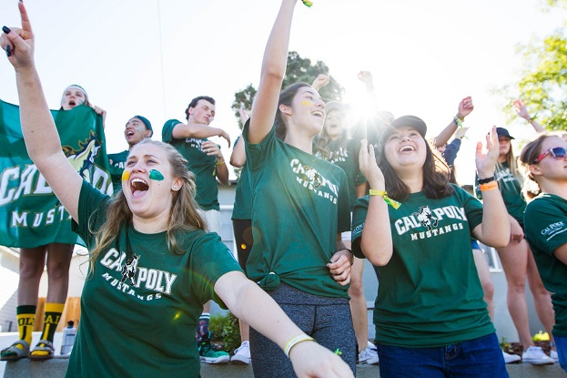 Group of Cal Poly students cheering while wearing green Cal Poly Mustangs t-shirts