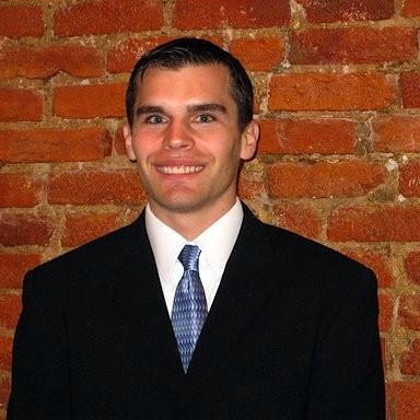 Nick wearing a suit and tie posing in front of a brick wall