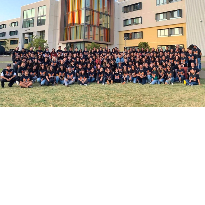Large group of students stand in front of a Cal Poly dormitory.