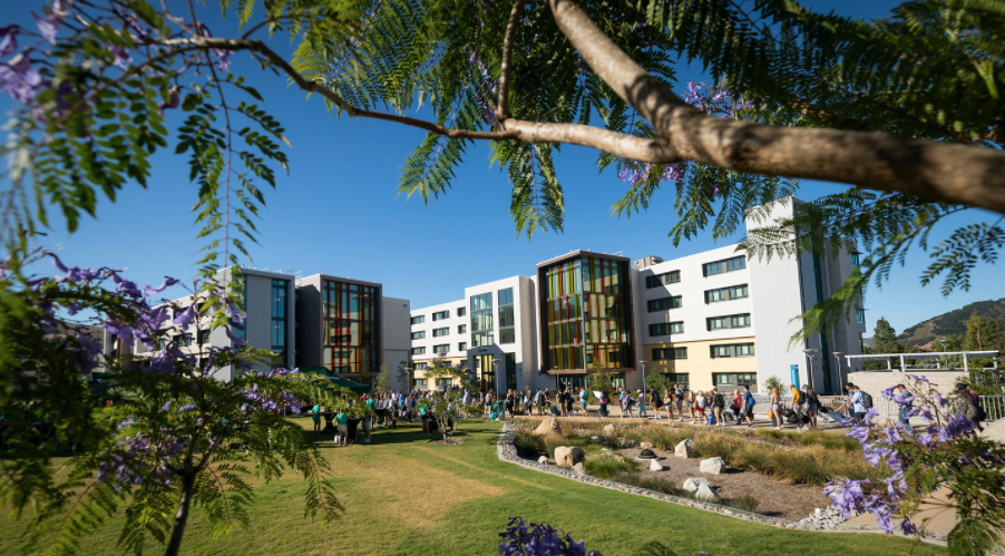 Image with Cal Poly building in the background and students standing in a line waiting to check in