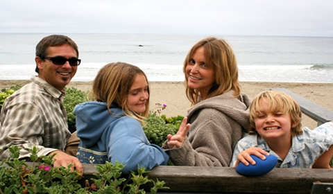 Jodi and family pose with the Pacific Ocean in the background