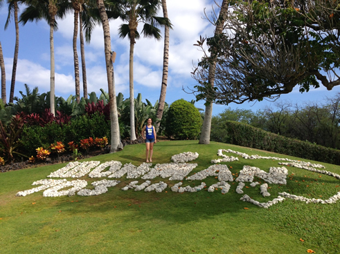 Blosser poses next to IRONMAN Hawaii sign
