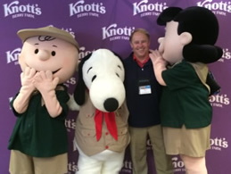Dr. Hendricks poses with Peanuts characters at the Cal Travel Summit