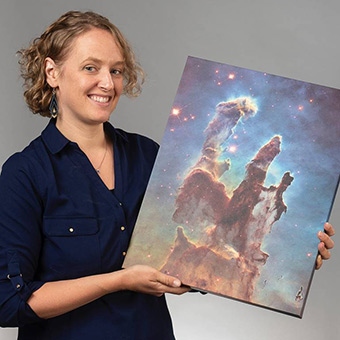Kate Follette holding a photo of an astronomical formation in space