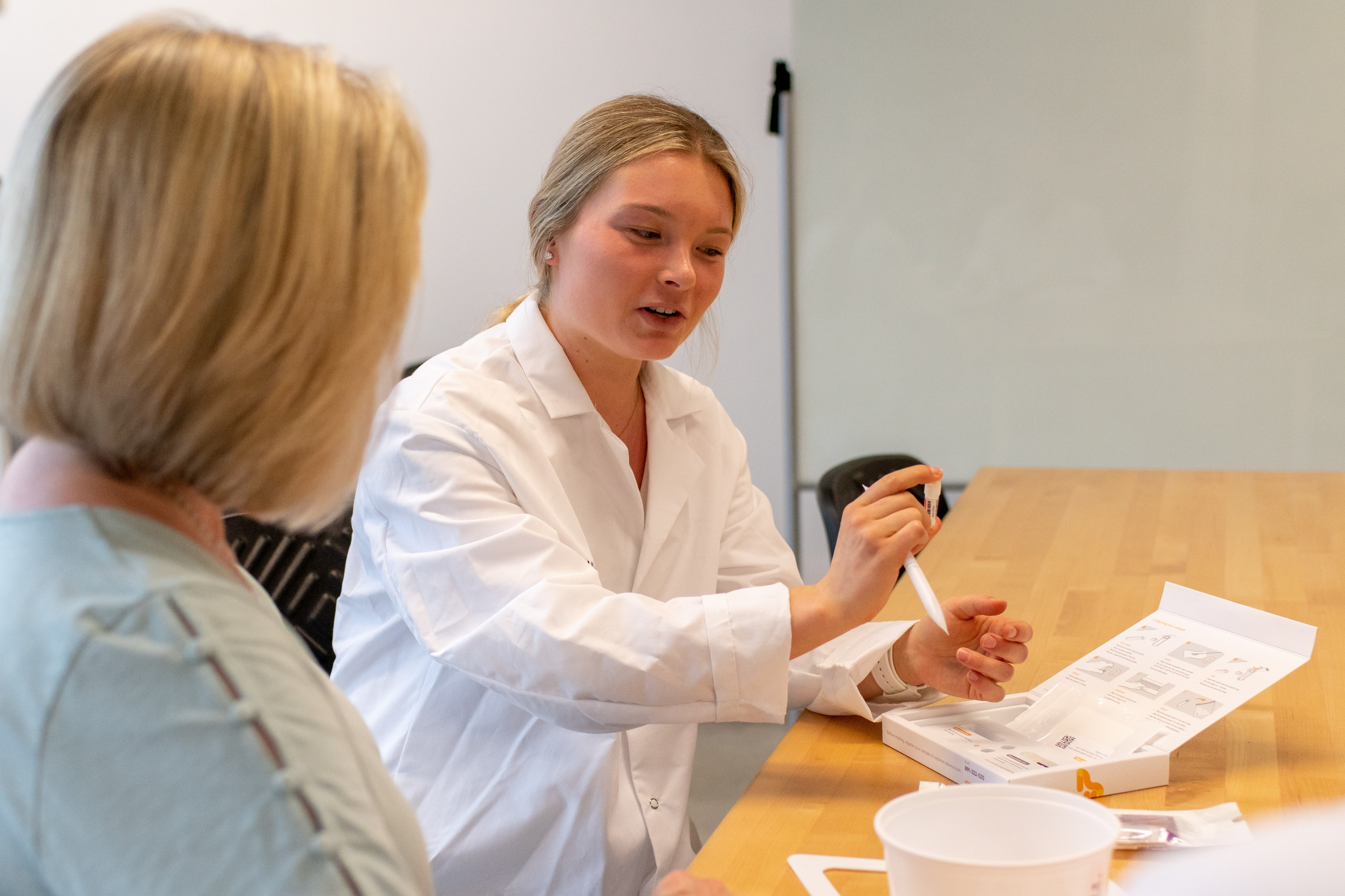 Didactic Program in Dietetics banner image; a female student practicing in a lab.