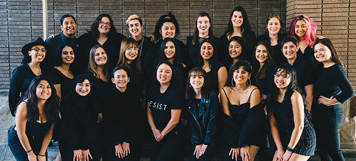 Photo of 24 people wearing all black and smiling at the camera.