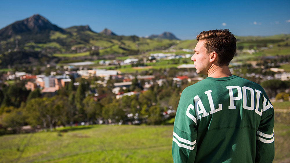 Cal Poly student looking over campus with landscape in background