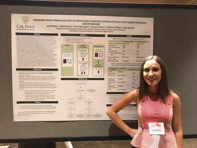 Leah Meuter smiling in front of a poster summarizing her research.