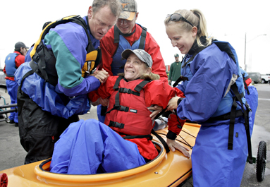 Kinesiology students help a woman into a kayak.