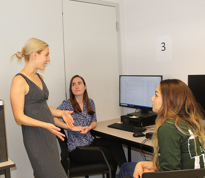 Professor Christine Hackman having a discussion with two students.