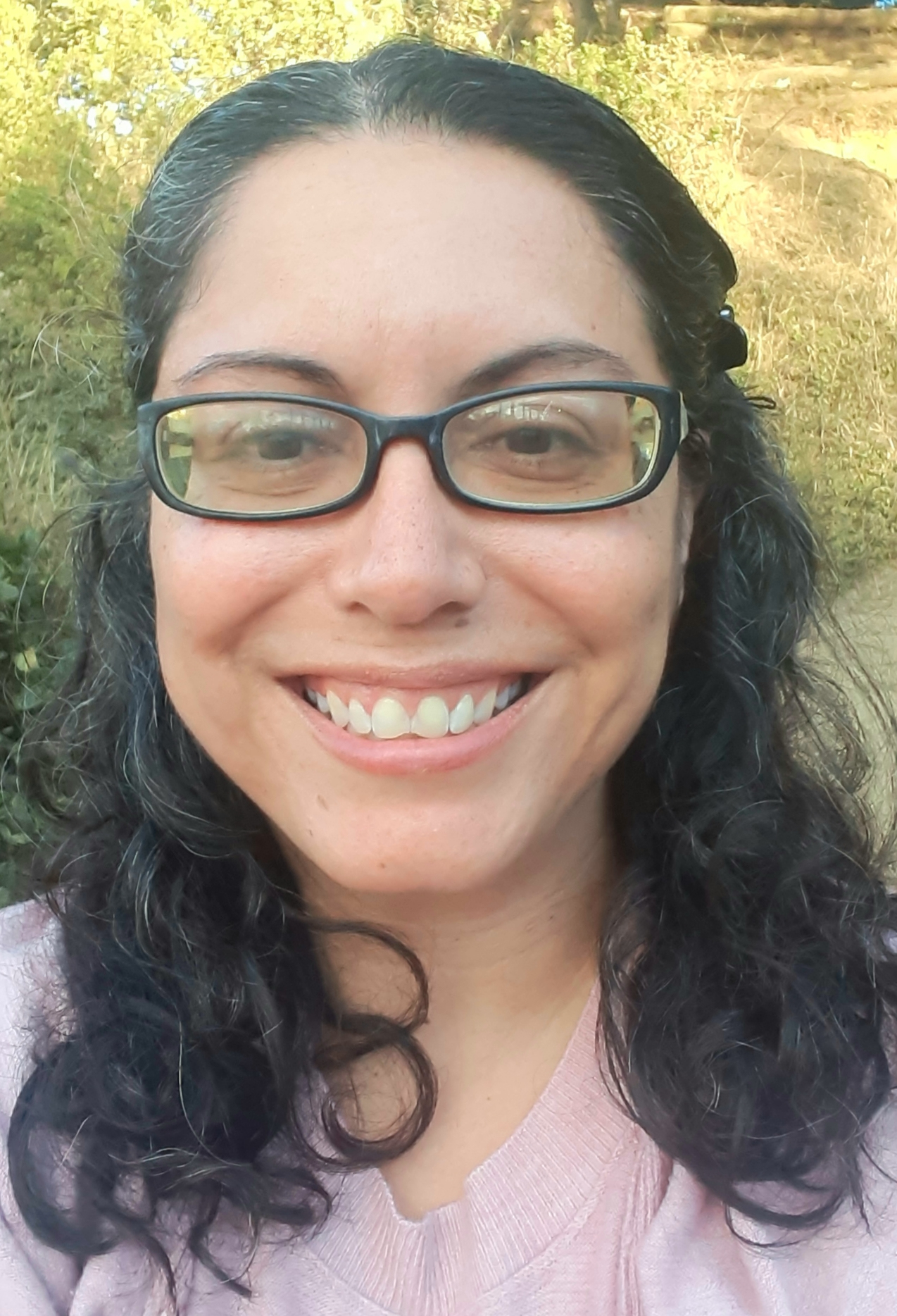 Photo of smiling woman with glasses, black and gray wavy hair and dark brown eyes.