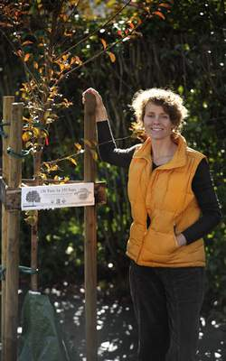 Photo of Tammara Norman standing by a recently planted tree