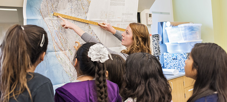 Woman points to map with ruler as children watch