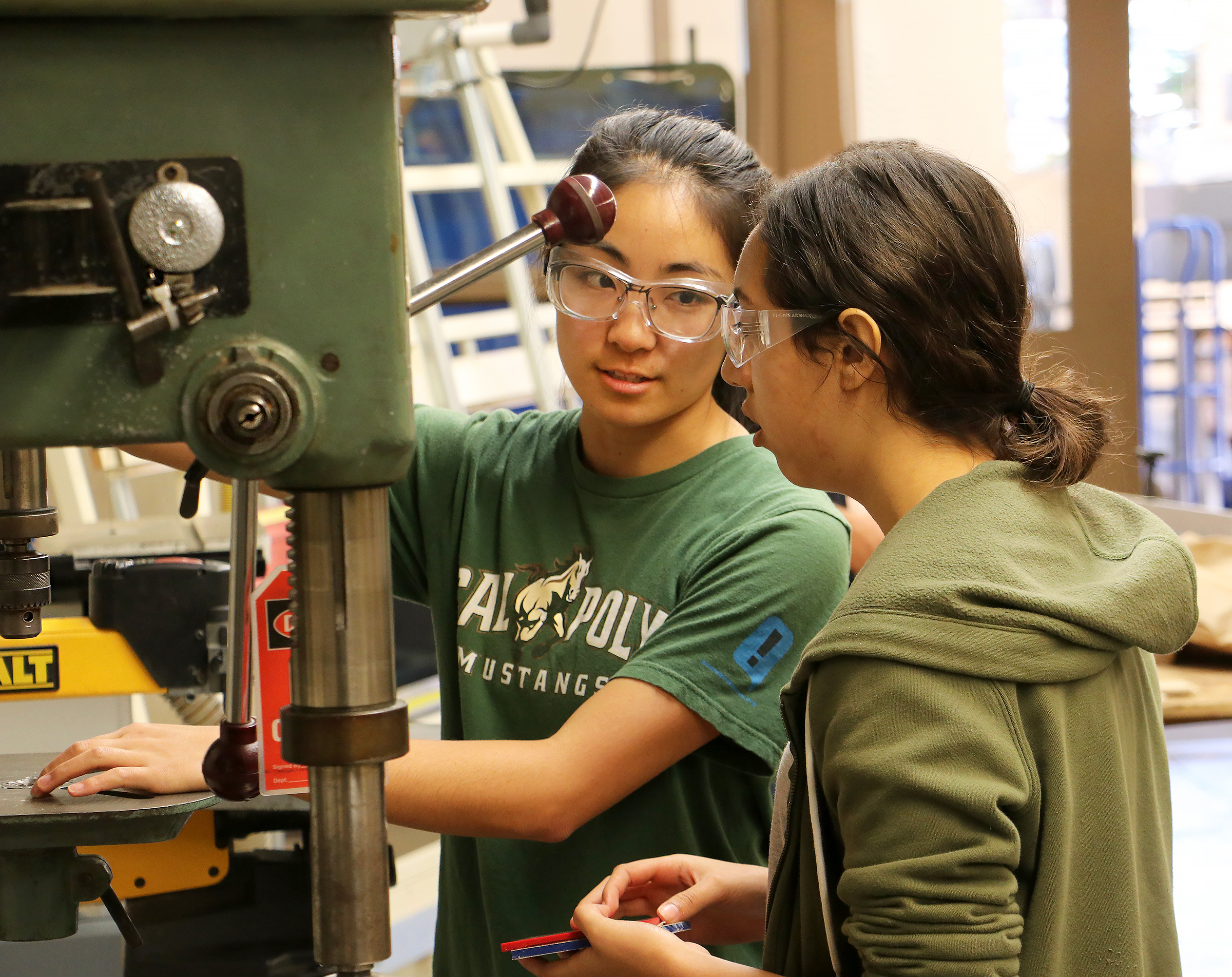 Two students wearing safety glasses and working with a shop drill press