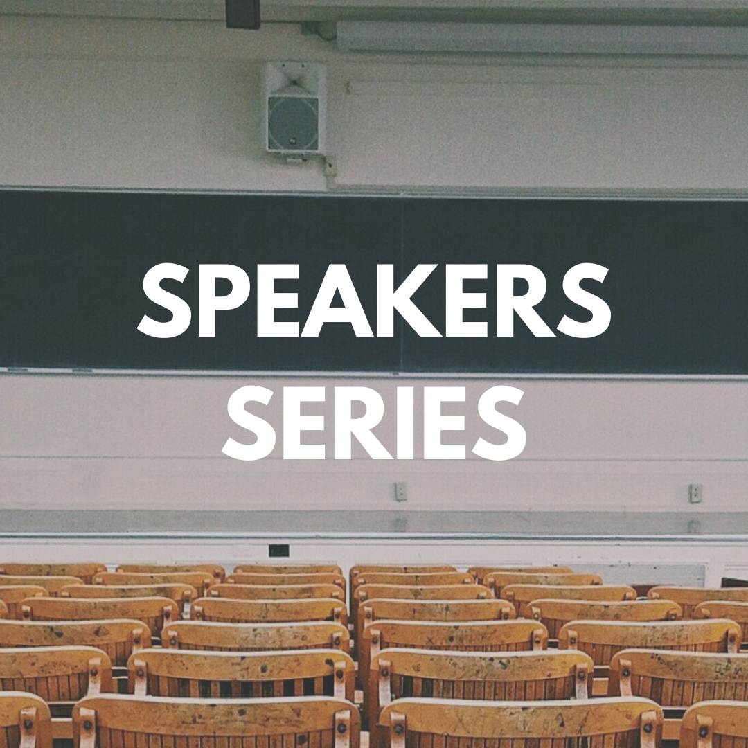 """Photo of an empty auditorium with the words """"Speaker Series"""" centered"""