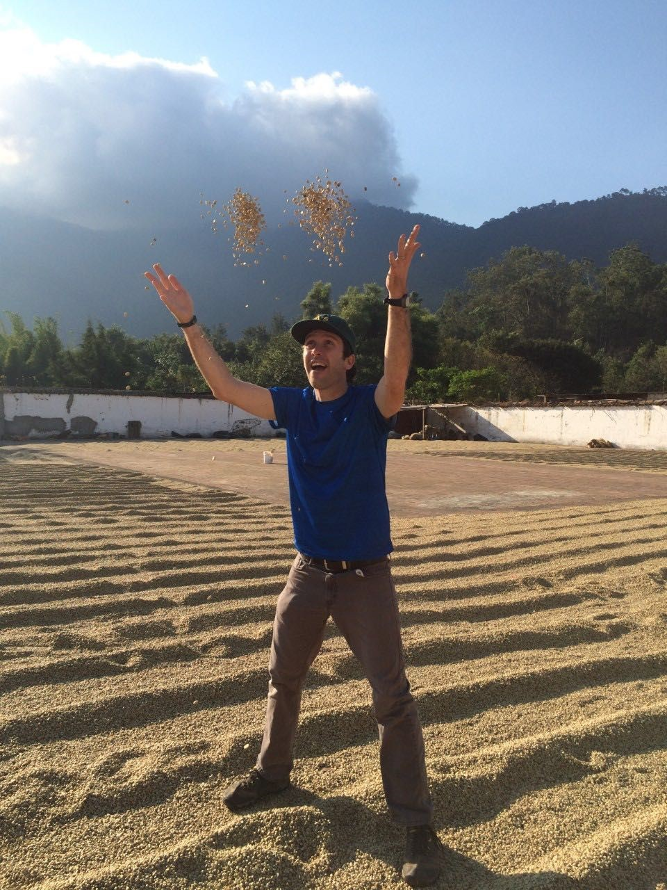 Nicholas Babin throwing grain in a field
