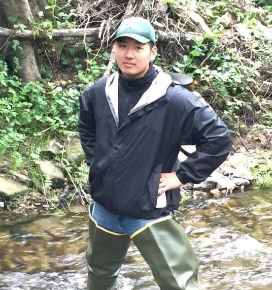 Danny Han standing in foliage