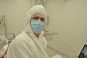 sam meijer fully covered in protective lab clothing, including a sterile mask.