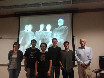 Five students standing with James Woolaway in front of a projector screen showing an infrared image of themselves.