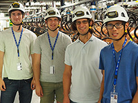 Professor and three students wearing hardhats and standing in an equipment room