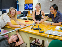 Four students in a classroom working on a piece of pipe