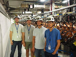 Professor and three students in equipment room wearing hard hats
