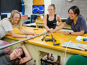 Four students constructing a radio antenna in a classroom