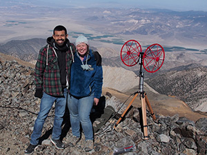 Professor and student with equipment on top of mountain