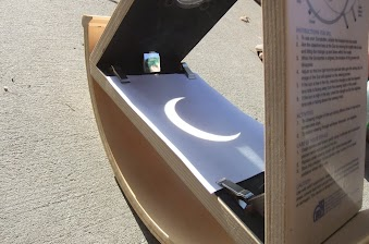 Solar eclipse viewing telescope showih the crescent-shaped image of the eclipsed sun on a white board beneath the telescope.