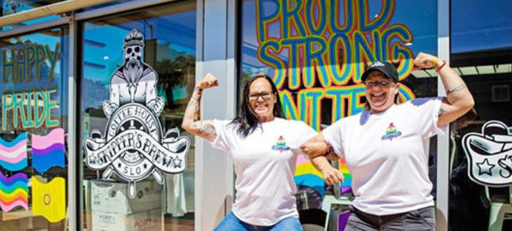An Image of the owners of Skippers Brew Coffee House in front of their Pride Decor.