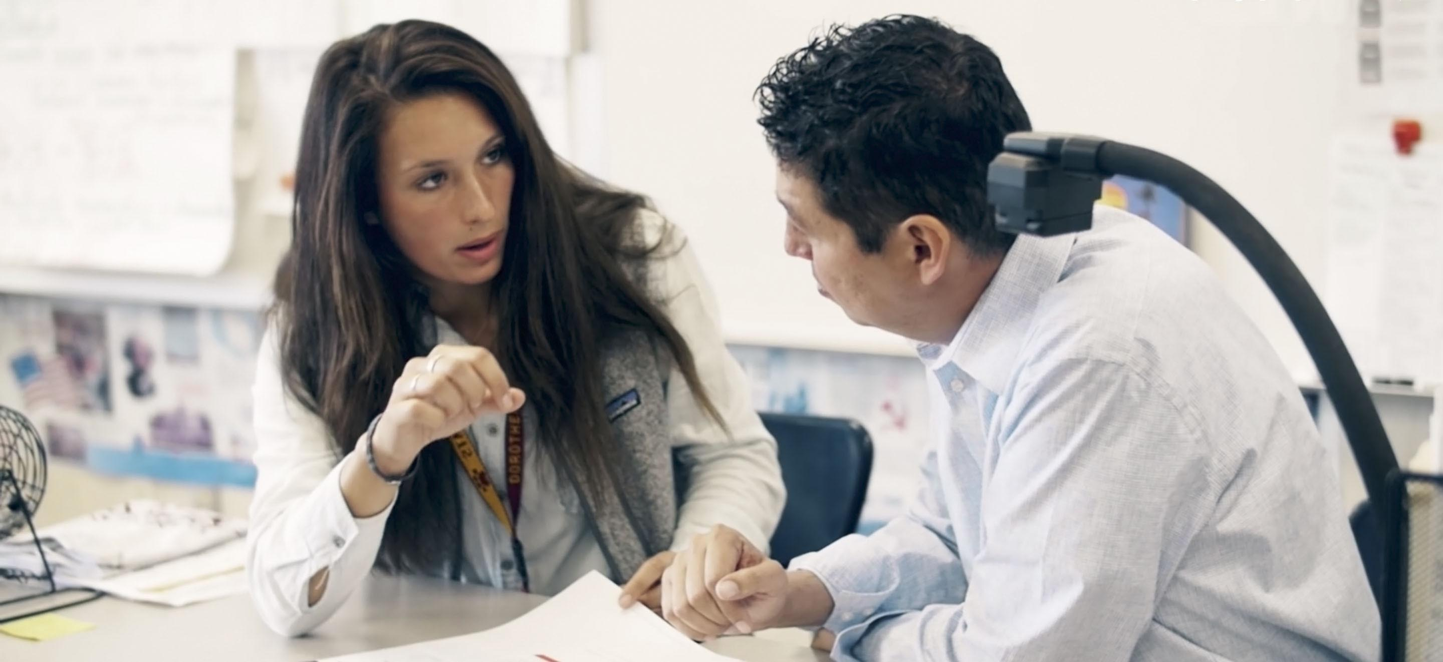 stock image. two adults reviewing papers in a classroom setting.