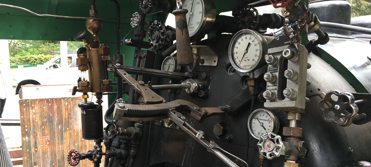 The gauges, knobs, and levers inside the cab of the 1/3 steam locomotive.