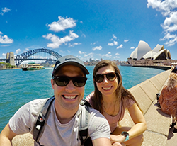 Man and woman in front of a body of water with the Sydney Opera House in the background