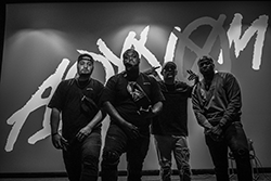 """Hip hop group in front of sign reading """"AOYNOM"""""""