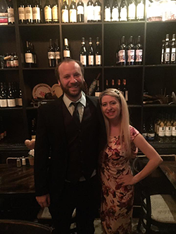 Man and woman standing in front of shelves of wine bottles