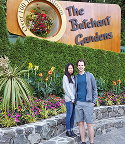 """Man and woman in front of sign that reads """"The Butchant Gardens"""""""