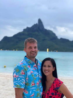 Aaron Hardiek and his partner at the beach with a large island in the background