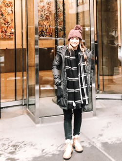 Jenna Harrelson in front of a building with glass walls and the address 5 Manhattan West