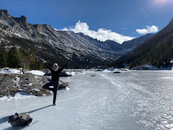 Julia Maddalena standing on one leg on a frozen river in the mountains