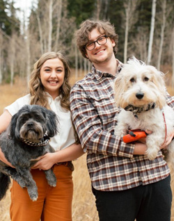 Maddie Lee with partner and two dogs in front of bare trees and evergreen trees