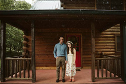 Suzanne Nelson Coulter and her partner on the porch of a log house