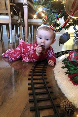 Baby and model train tracks underneath Christmas tree
