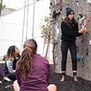 Students prepare to climb at Cal Poly's rock climbing wall