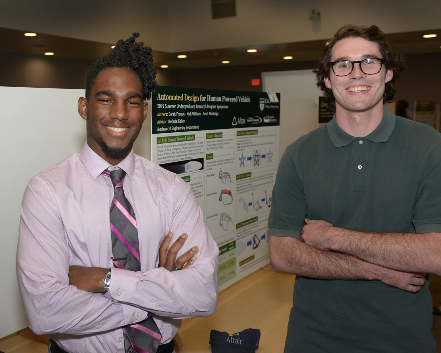 two College of Engineering students in front of a research poster