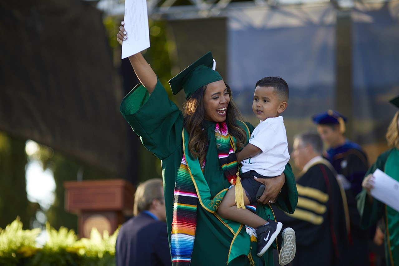 Cal Poly graduate crossing graduation stage carrying her son