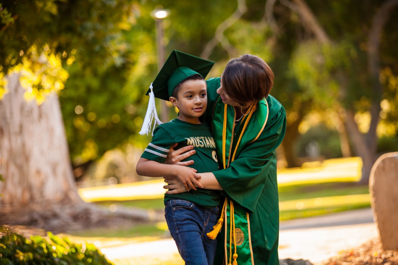 Cal Poly student in cap and gown with son