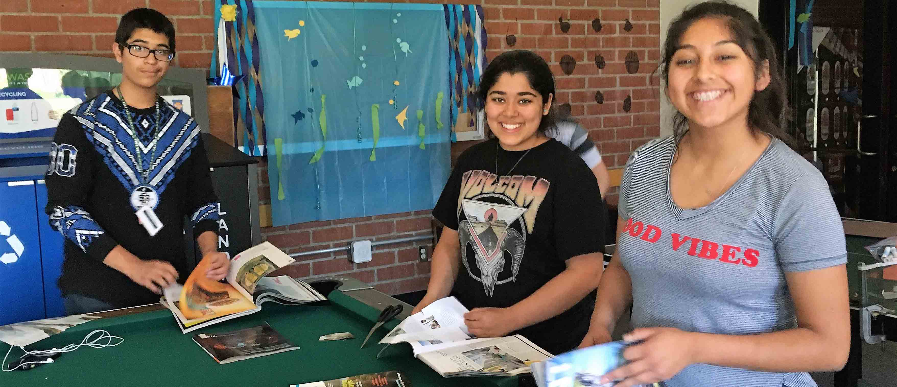 Three students cutting magazines